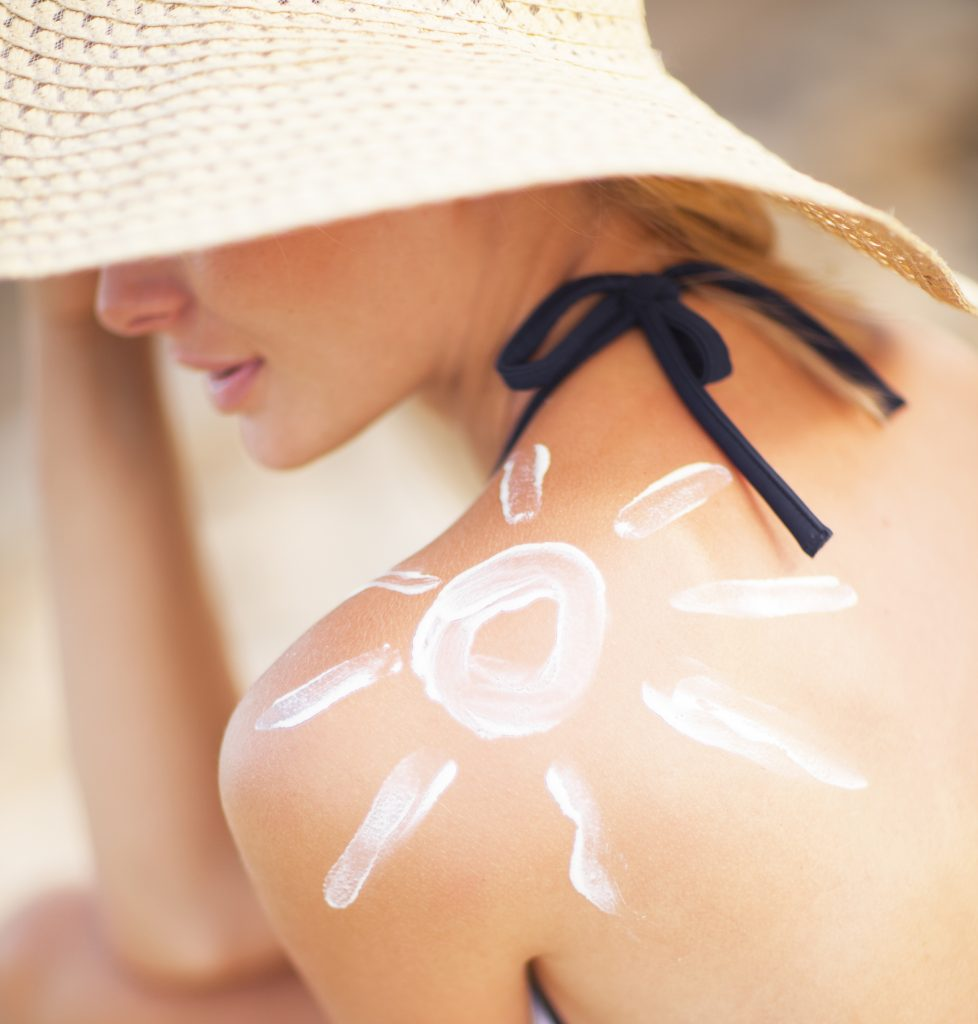 A woman with a sun painted on her shoulder in sun screen