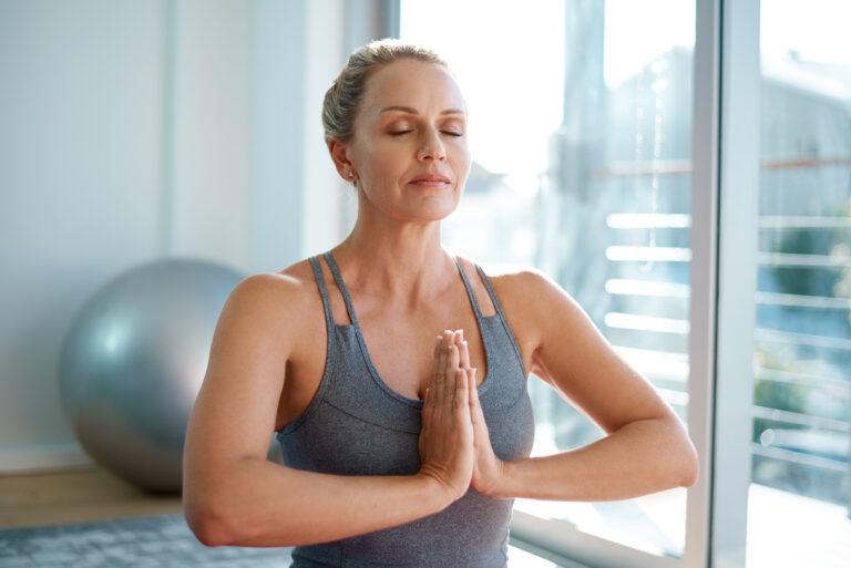 Mature woman meditating at home