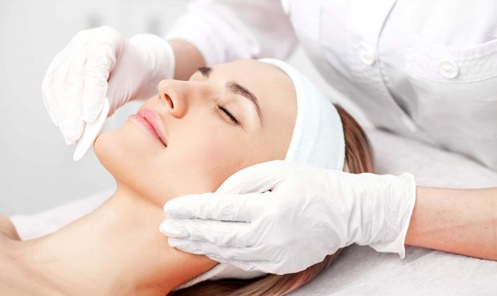 Professional young cosmetologist is curing female skin