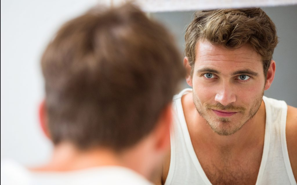 Smart young man looking at himself in mirror at bathroom